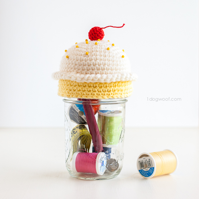 Crochet cupcake pincushion on top of a mason jar sewing kit | via 1dogwoof.com