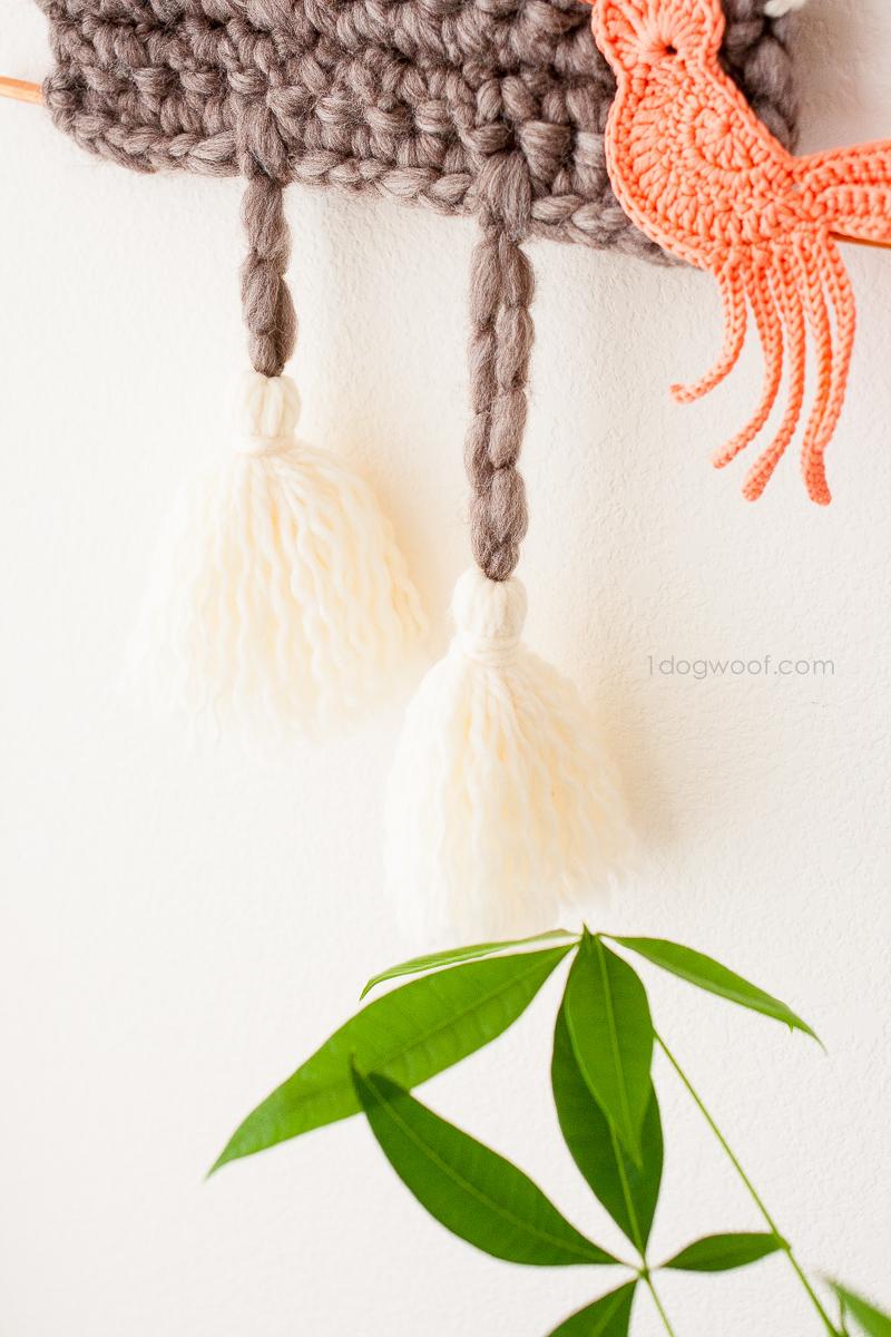 Big fluffy tassels on a yarn cuckoo clock wall hanging