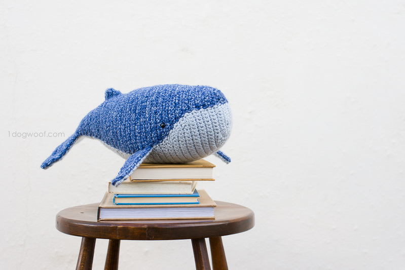 Baby Humpback crocheted whale sitting on a stack of books