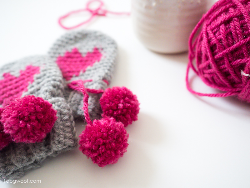 Adorable pom poms on heart motif baby mittens.
