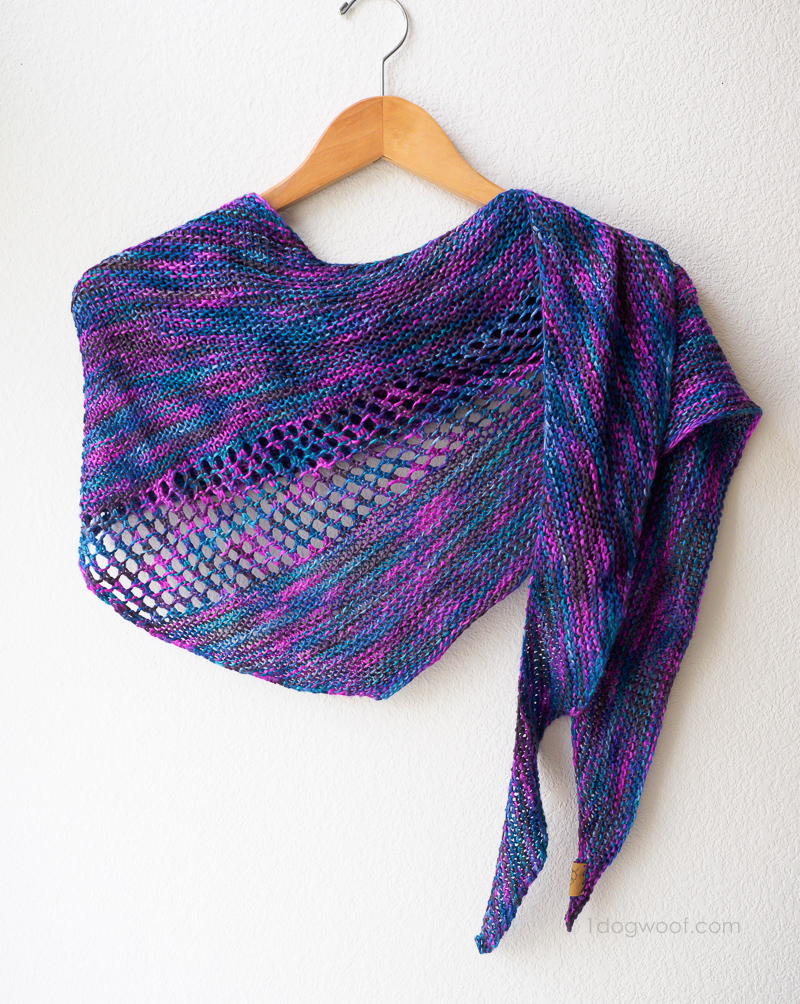Asymmetrical shawl scarf on hanger.