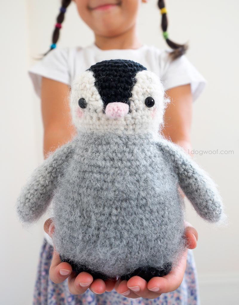 little girl holding fuzzy baby penguin amigurumi