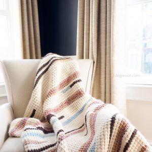 Tunisian crochet pattern for Sunset Stripes Blanket on armchair
