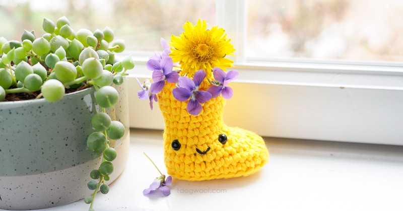 yellow crochet rain boot with purple flowers, sitting on windowsill