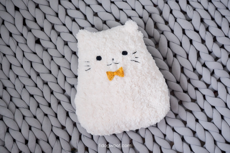 stuffed cat pillow on chunky blanket