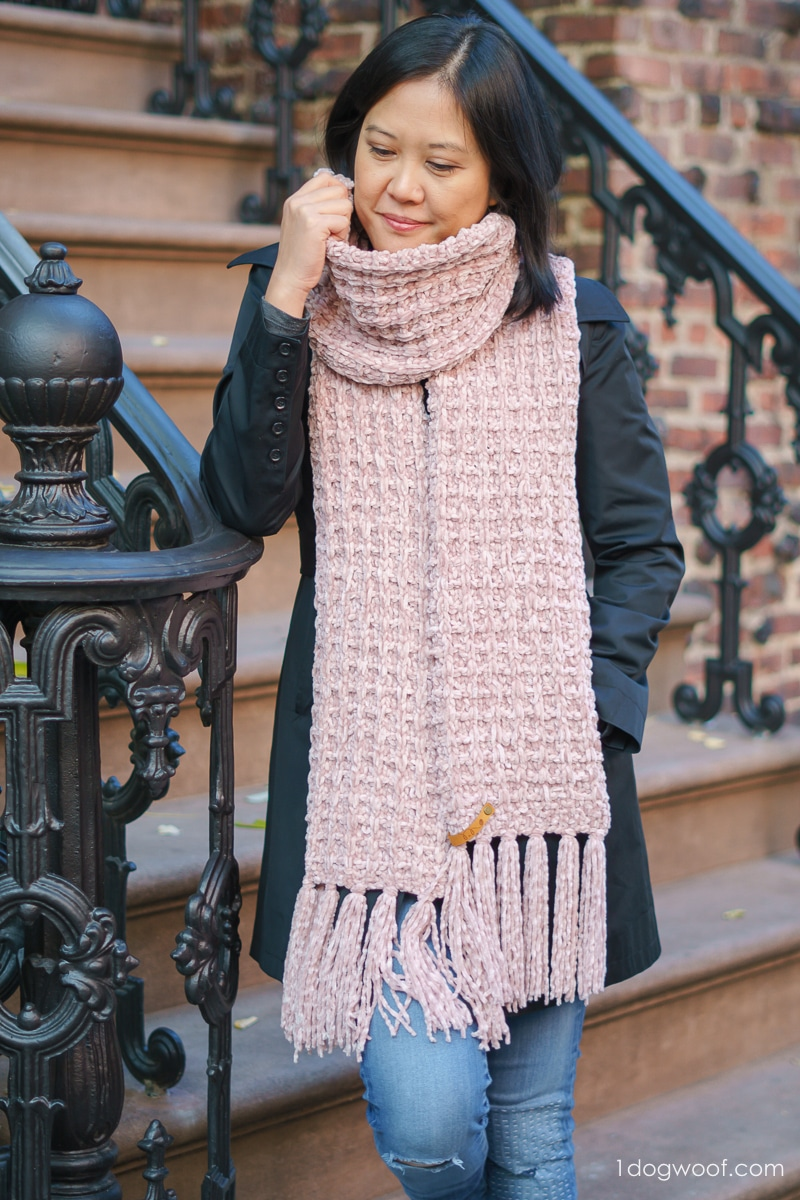 woman holding waffle-knit scarf standing on step