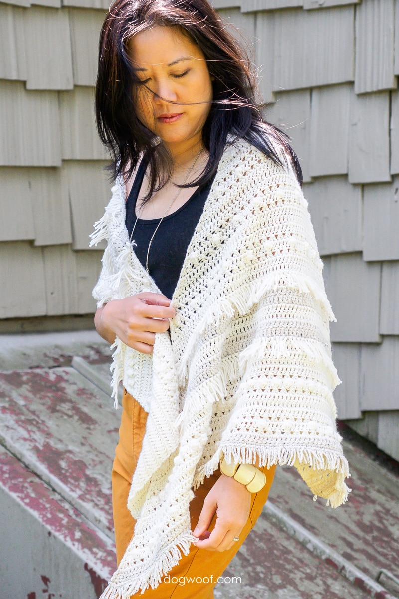 model wearing crochet fringe shawl