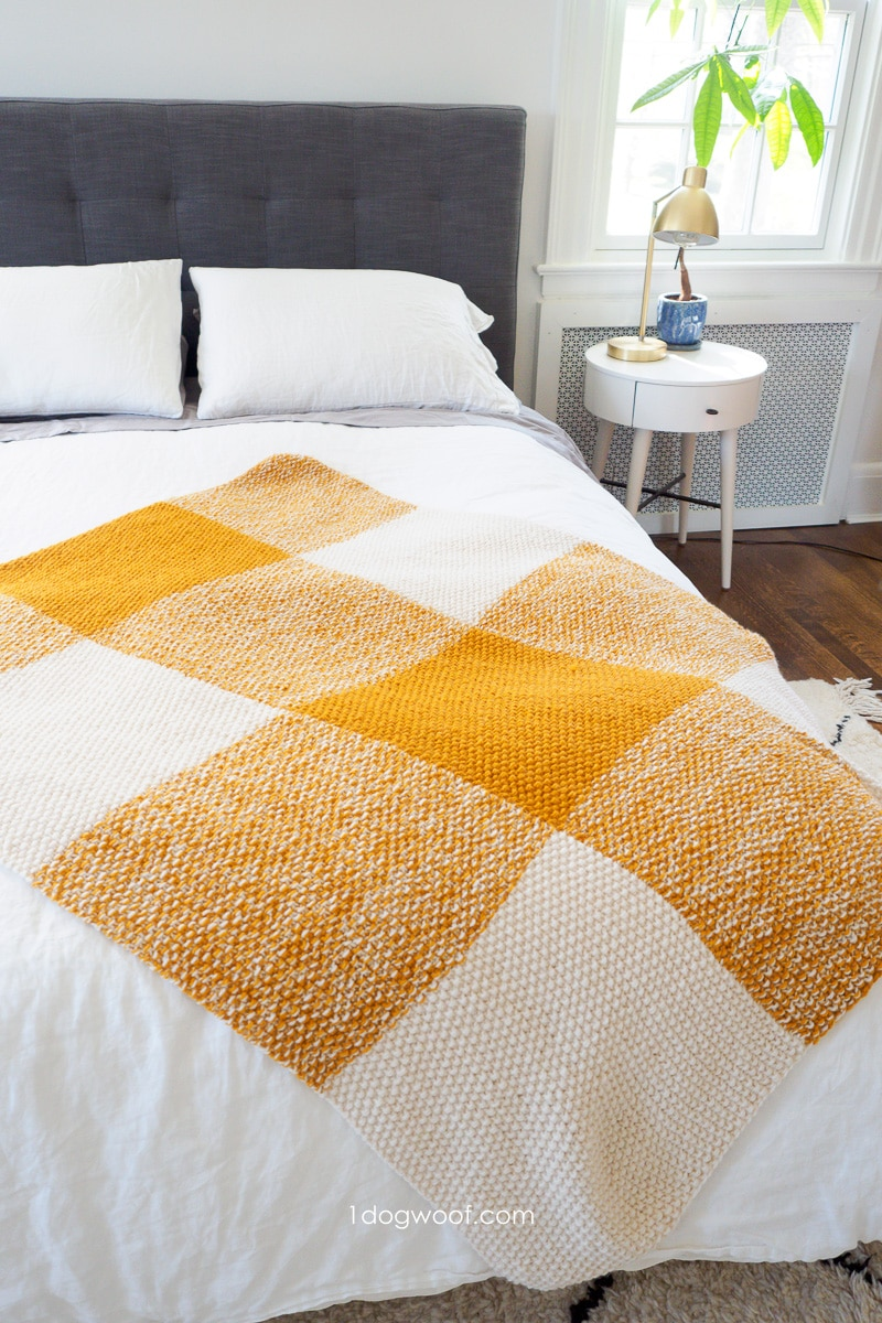 gold and cream buffalo plaid throw on bed