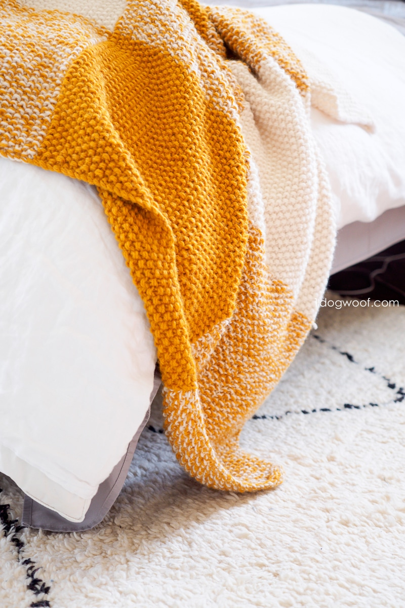 seed stitch knitted blanket draped over bed