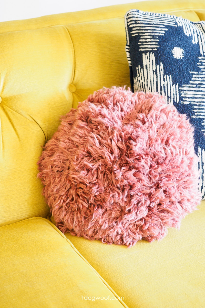 pink shag crochet pillow on yellow couch