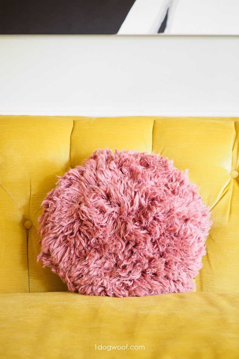 pink shag throw pillow on yellow couch