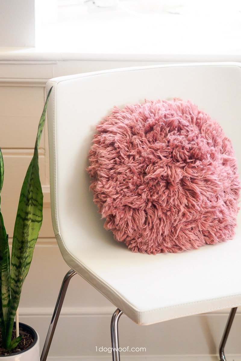pink shag accent pillow on white chair