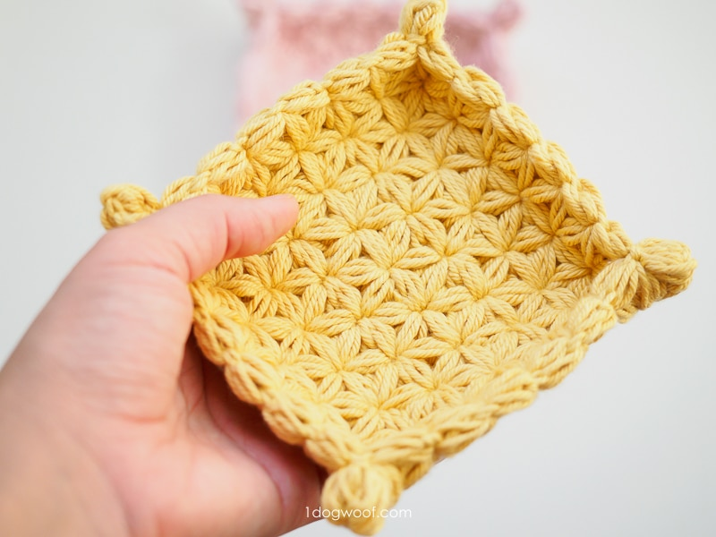 holding a small yellow crochet jewelry dish