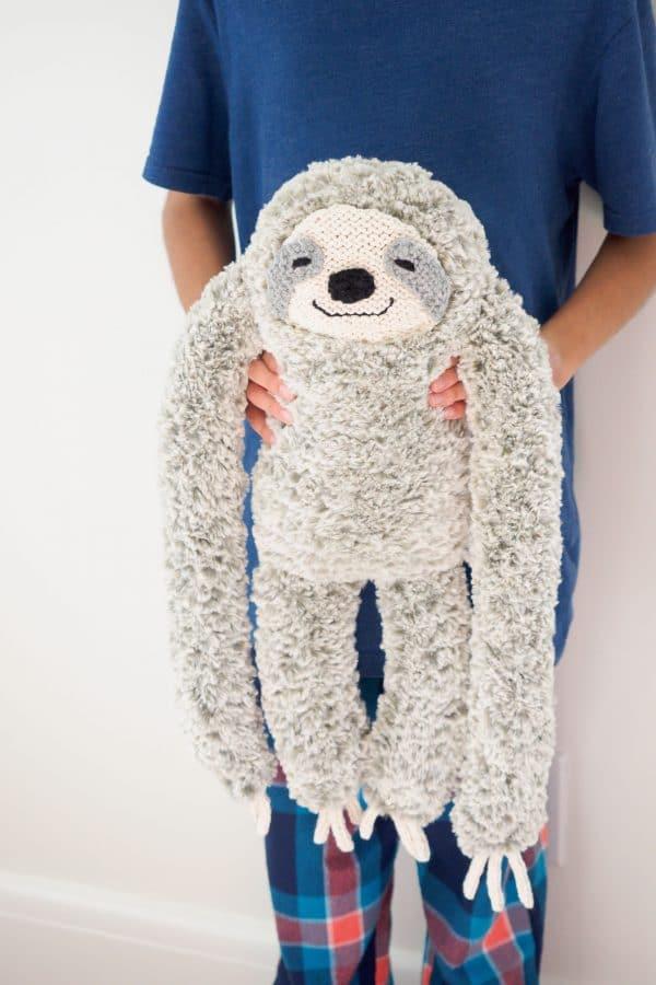 child holding plush sloth