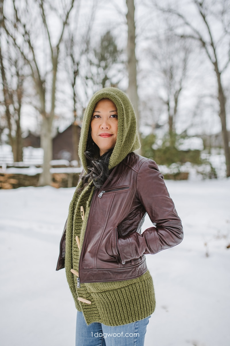 knit vest with hood layered under leather jacket