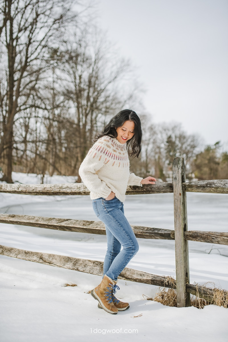 chunky sweater and snowboots by icy pond